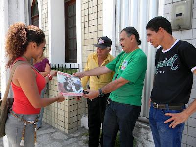 Organizadores do evento recebem o jornal Classe operária que comemora os 90 anos do partido.