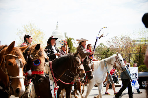 Cowboys and Indians ride horses in protest march