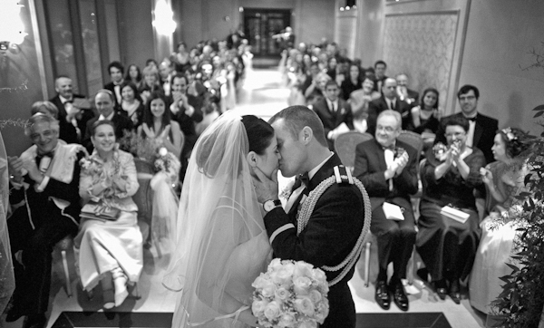 Bride and groom's kiss at the alter in front of their guests. Captured by DelCastillo Photography.