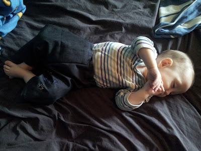 Sleeping baby on bed, wearing new dark denim trousers and white/blue/green stripy top