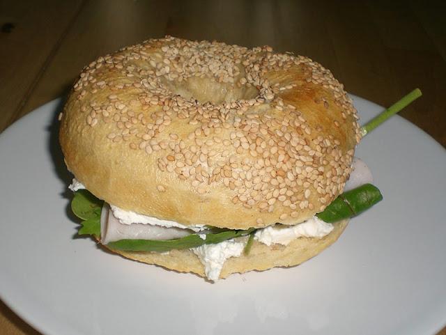 frisch gebackener Sesam-Bagel mit Frischkäse mit Spinatblättern, Wintersalat und Putenbrust