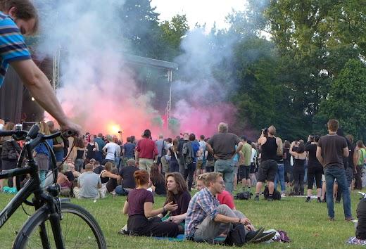 Zuhörerinnen und Zuhörer auf der Wiese, im Hintergrund Bühne mit Rauch- und Lichteffekten.