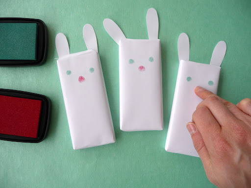 Using another finger with a red stamp pad, print noses on your bunnies.