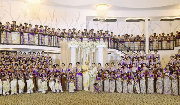Sri Lankan wedding couple Nisansala and Nalin pose for photographers alongside their wedding party during their Guinness World Record-breaking wedding in Negombo, some 30kms north of Colombo, on November 8, 2013. Including 126 bridesmaids, 25 best men, 20 page boys and 23 flower girls the wedding breaks the previous record, held by a wedding in Bangkok that included 96 bridesmaids.