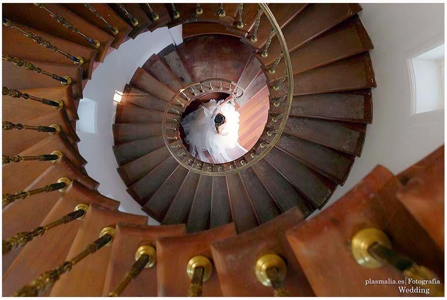 fotografía de la boda disparada desde la parte más alta de una escalera de caracol.