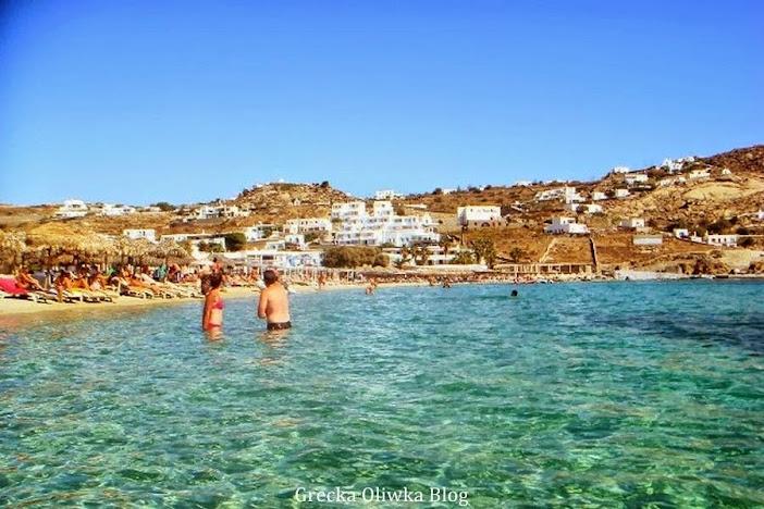 Dwoje trurystów w strojach kąpielowych zanurzeni do pasa greckim morzu, na plaży leżaki i parasole trzcinowe