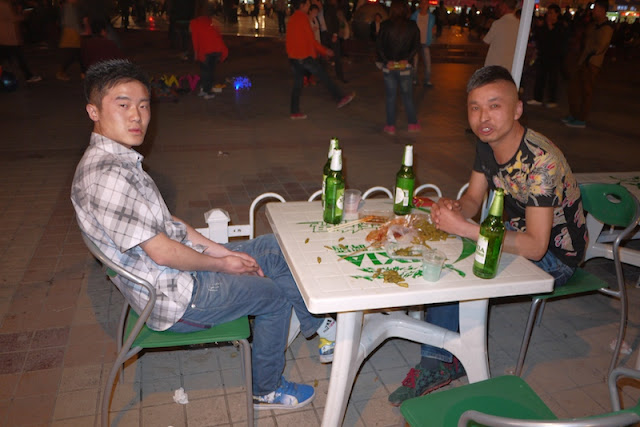 two young men sitting at a table with several beer bottles in Yinchuan, China