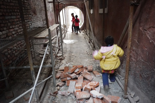 three children running through a construction area