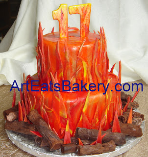 Two tier fondant flames bonfire custom designed birthday cake with fondant logs and 17 topper