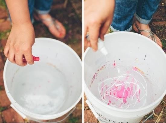 Jogue tinta em um balde com água