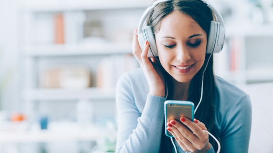 woman listening to music through headphones and looking at her phone
