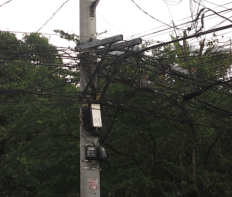 a jumble of cables on a utility pole