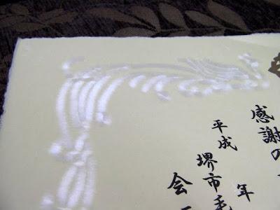 手漉き和紙の賞状、鳳凰の柄を白の繊維で漉き合わせた作製事例