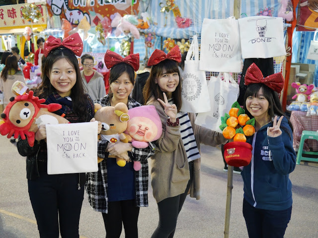 four female college students wearing large read bows on their heads and holding bags and stuffed toys