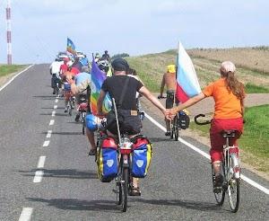Friedensradfahrer und Friedensradfahrerinnen fahren bergauf, die letzten beiden Händchen haltend.