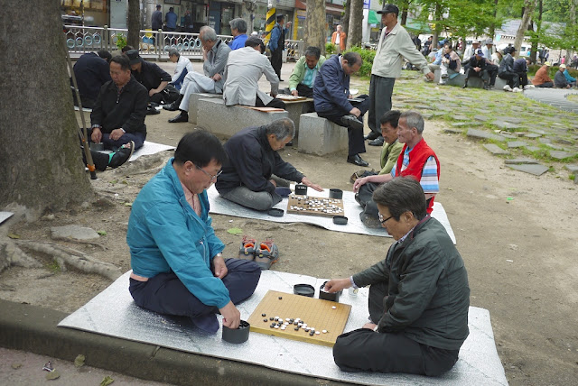 two men playing baduk (Go) at Jongmyo Park in Seoul