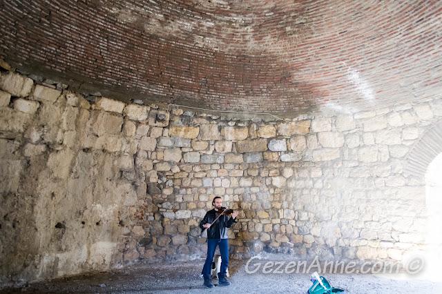 Sığacık kalesinin kubbeli bölümünde keman çalan bir sanatçı, Seferihisar