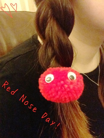 A close up of a plait of the hair being secured by a pom pom. The pom poms have googly eyes and are red to celebrate red nose day.