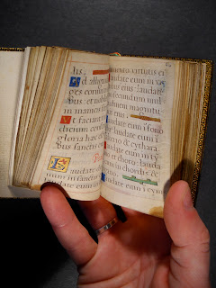 A photograph of a hand holding a small book open. The pages are handwritten with decorative initials.
