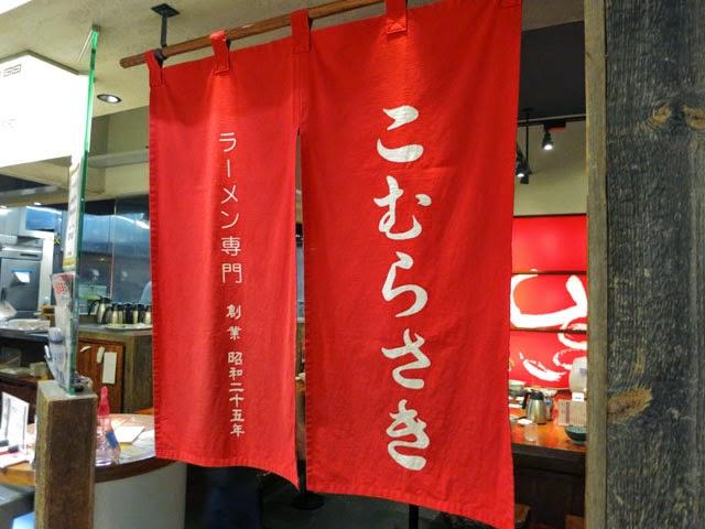 店頭に掛けられた「ラーメン専門こむらさき」と書かれた赤いノレン