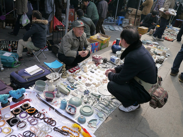 "seller wearing a Chinese People's Liberation Army ""Mao"" cap at an outdoor antique market in Changsha, China"