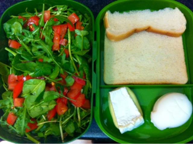 Bento lunch box with rocket salad, brie, a slice of bread and a fish shaped hard boiled egg (use a rice mould to press the egg!)