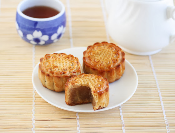 three traditional moon cakes with one sliced open to show the filling