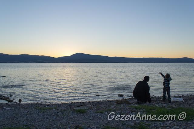 Günbatımında Özbek Köyü limanında denize taş atarken, Urla İzmir