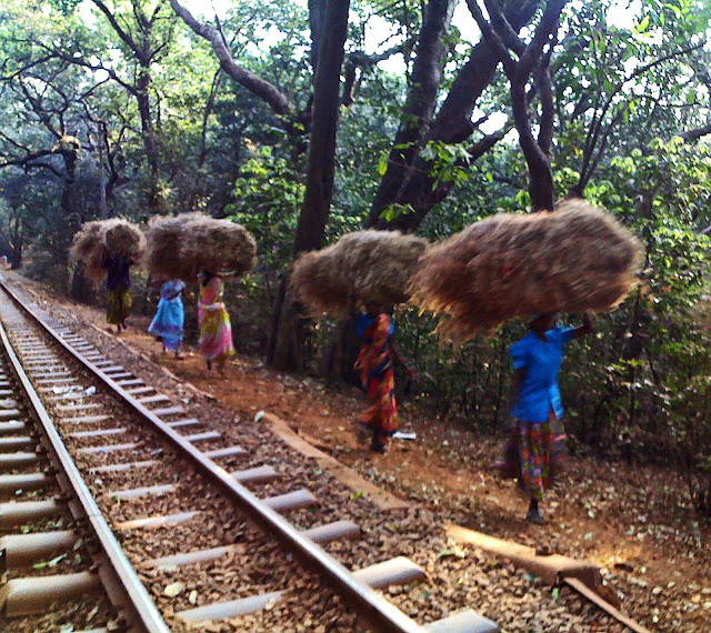 women carrying loads of hay