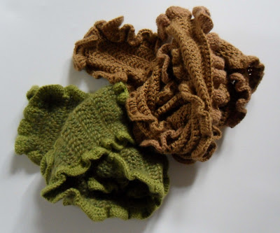 Two crinkle edged crochet scarves. The first is earth green with flecks of tan the second is dark tan