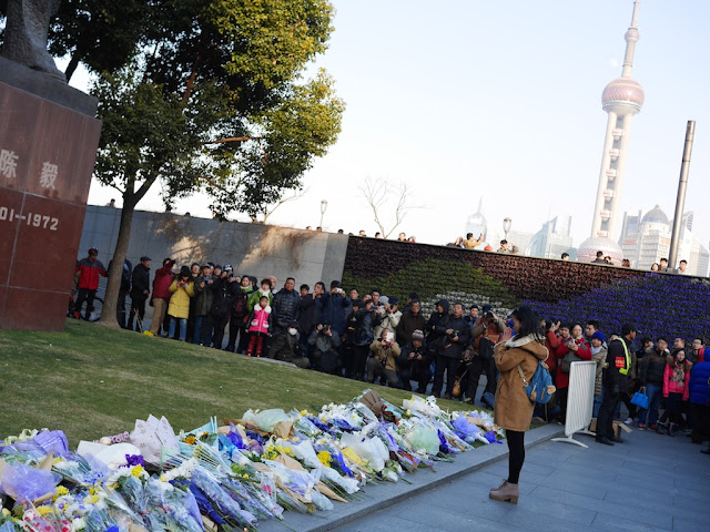 young woman praying in front of a memorial for people killed and injured by the New Year's Eve stampede in Shanghai