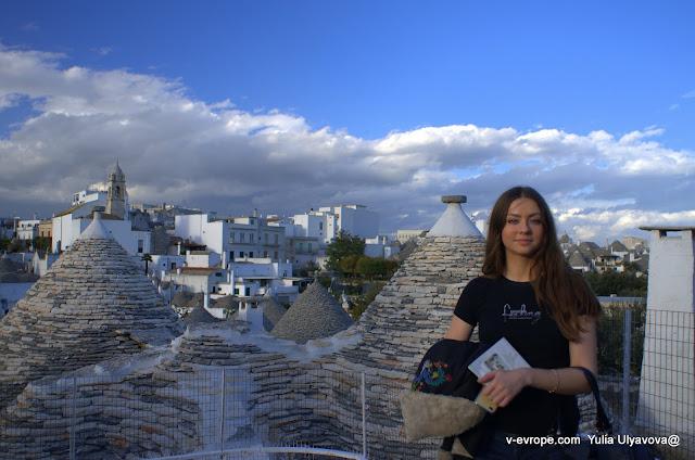 Юлия Ульянова на фоне труллей на одной из смотровых площадок Альберобелло