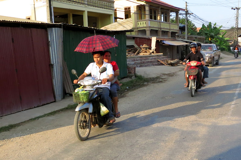Woman on moped with umbrella