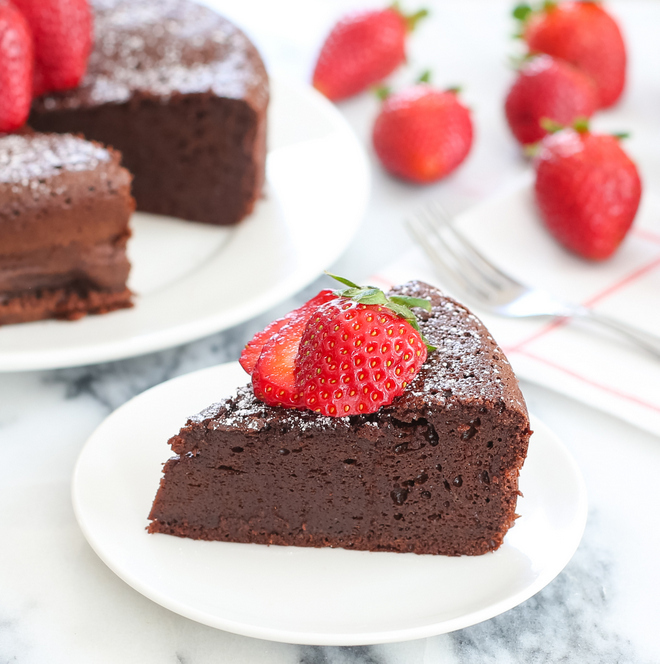 a photo of a slice of flourless chocolate cake garnished with fresh strawberries
