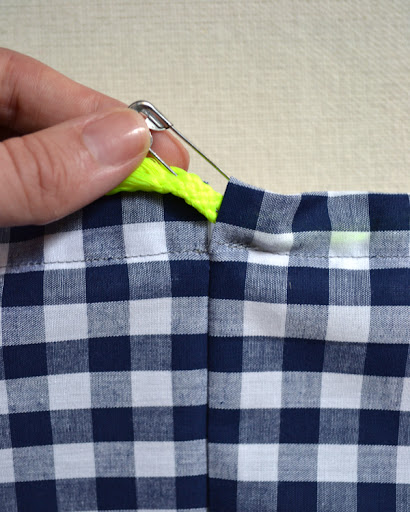Thread trim through channel by attaching a large safety pin to the end of one of the pieces of trim.