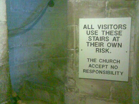 ancient church stairs with modern health & safety notice accepting no responsibility