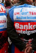 Demonstranten, am Rücken befestigt: »um fair teilen, Reichtum besteuern, Banken enteignen!«.