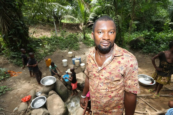 A youth leader who lives near one of Wilmar's Nigerian oil palm projects shows an alternative water hole the community has dug as a result of the plantation polluting its main water source. Photo courtesy of Environmental Rights Action-FoE Nigeria.