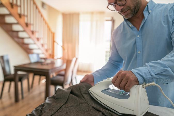 Businessman ironing suit jacket