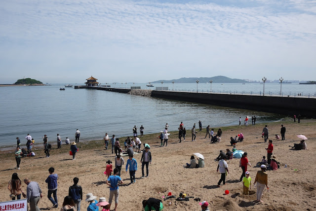 Qingdao's Huilan Pavilion and pier with a beach in the foreground