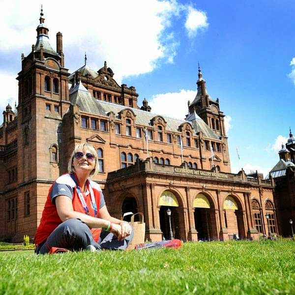 Commonwealth games Volunteer Jane Whitaker sits on the grass outside Kelvingrove Museum and Art Gallery next to the Lawn Bowls arena in Kelvingrove Park, Glasgow on July 22, 2014, ahead of the opening of the 2014 Commonwealth Games in the city of July 23, 2014.