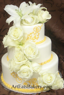 Three tier white fondant unique custom wedding cake with yellow scroll piping, white fresh roses and lilies