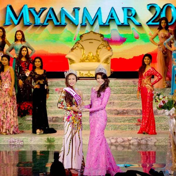 Miss Universe Myanmar 2014 Sharr Htut Eaindra, center left, is crowned by Miss Universe Myanmar 2013 Moe Set Wine, center right, during a pageant in Yangon, Myanmar, Saturday, July 26, 2014.