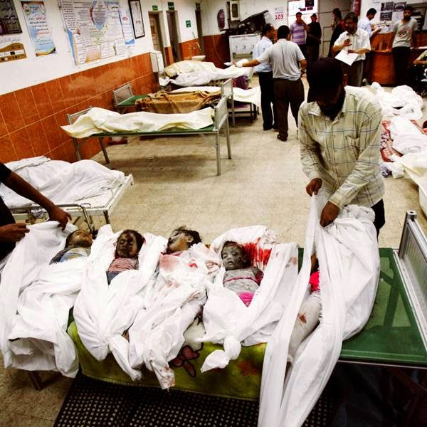 Palestinian medics wrap in burial shrouds the bodies of children from the Al Najar immediate and extended family, after an Israeli air strike on their building of four apartments, at Nasser hospital in Khan Younis, Gaza Strip.