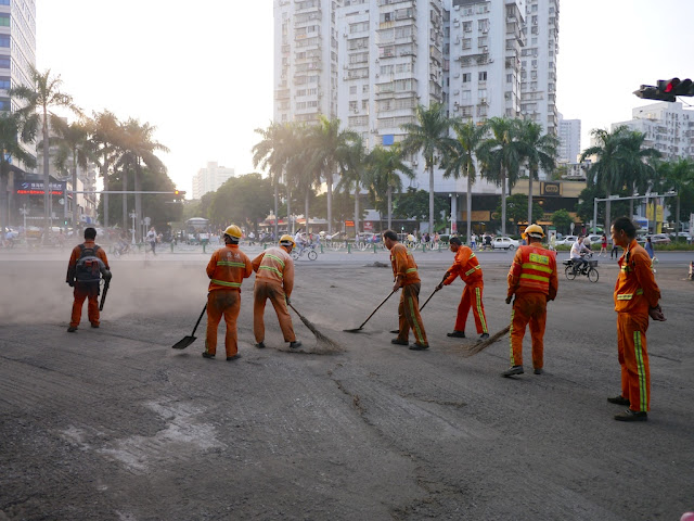 workers removing gravel from a road using brooms and shovels