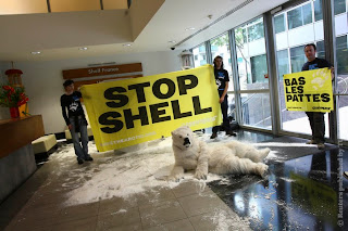 "Environmental activists from the Greenpeace organization hold a banner reading ""Stop Shell"" beside an activist dressed up as a polar bear during an action at the Shell Company headquarters in Colombes near Paris July 19, 2012. The protest was staged to demand that oil companies halt their exploration plans in the Arctic. REUTERS/Handout/Nicolas Chauveau/Greenpeace  (FRANCE - Tags: ENERGY CIVIL UNREST ENVIRONMENT ANIMALS) NO SALES. NO ARCHIVES. FOR EDITORIAL USE ONLY. NOT FOR SALE FOR MARKETING OR ADVERTISING CAMPAIGNS. THIS IMAGE HAS BEEN SUPPLIED BY A THIRD PARTY. IT IS DISTRIBUTED, EXACTLY AS RECEIVED BY REUTERS, AS A SERVICE TO CLIENTS"