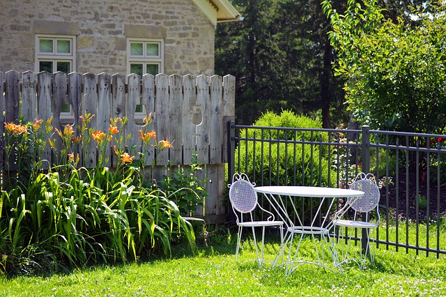 A quiet corner of a backyard with a white metal table and  two chairs