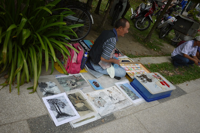 man selling drawings at an outdoor market in George Town, Penang, Malaysia