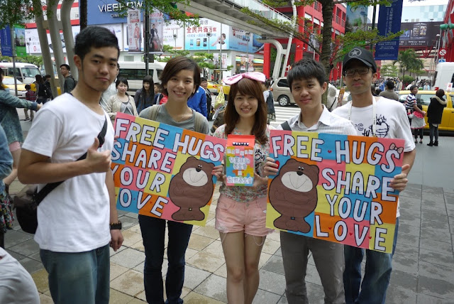 5 youth in Taipei holding signs reading 'Free Hugs Share Your Love'