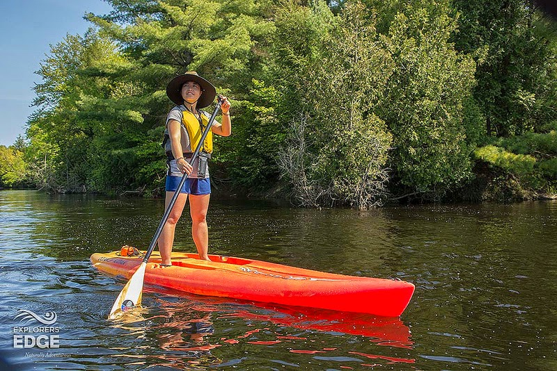 Jill on a stand up paddle board fighting the current of Muskoka River, one of the many outdoor things to do in Ontario